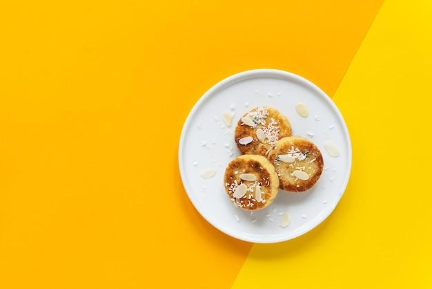 黄色とオレンジ色の背景にプレートに豆腐チーズ パンケーキ