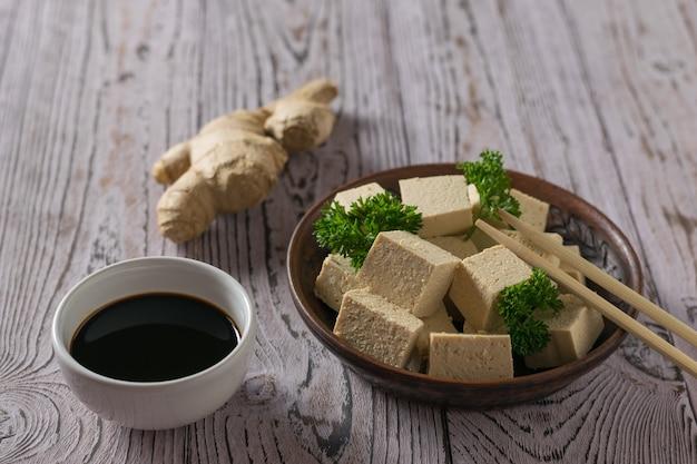 Сыр тофу, соевый соус и корень имбиря на деревянном столе