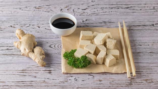 Сыр тофу с корнем имбиря, зеленью и соевым соусом на деревянном столе. соевый сыр. вегетарианский продукт.