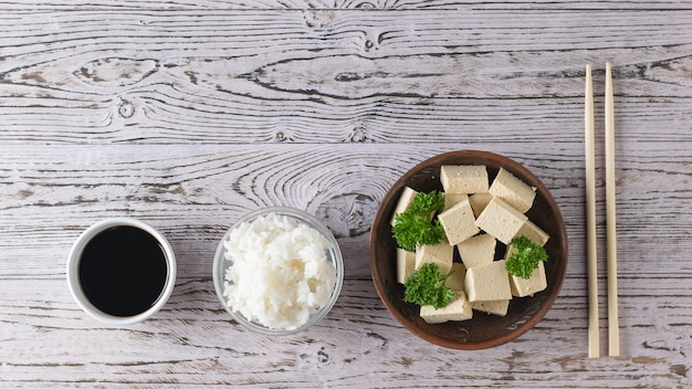 Tofu cheese with parsley, soy sauce and rice on a wooden table. soy cheese. vegetarian product. flat lay.
