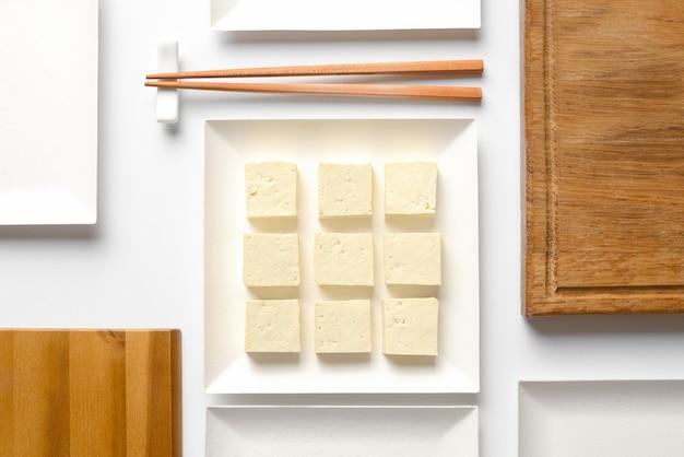 豆腐はさいの目に切って、大豆の栄養製品の正方形のプレートの概念的なテーブル設定で提供されます