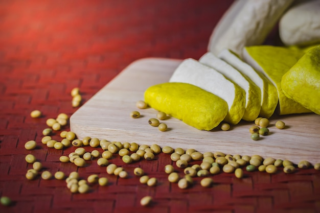 Tofu is sliced on a wooden cutting board and soybean seeds scattered.