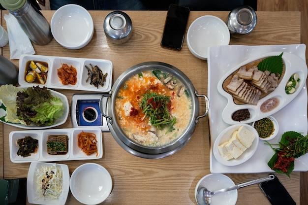 Острый суп тофу, сваренный с овощами и маринованными огурцами, и полосатая свинина традиционной корейской кухни на столе