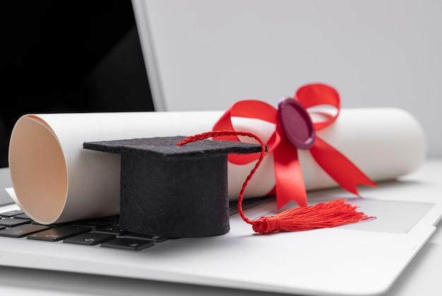 ノートパソコンのトーガ帽子と卒業証書 Premium写真