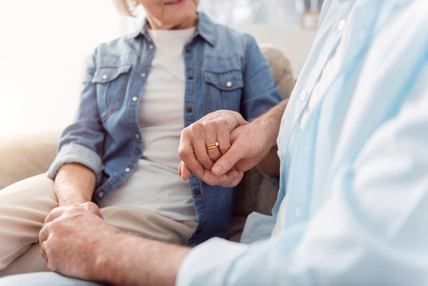 Together till end. the close up of happy elderly couple sitting on the sofa and holding hands, the focus being on the hand of the wife with an engagement ring on it