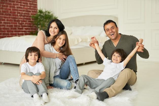 Вместе в полный рост веселая латинская семейная девочка-подросток и маленькие мальчики-близнецы улыбаются