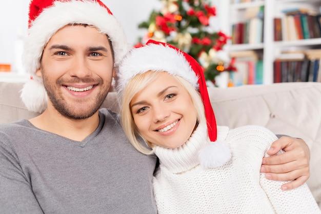 크리스마스 이브에 함께. 소파에 앉아 카메라를 보며 웃고 있는 아름다운 젊은 부부