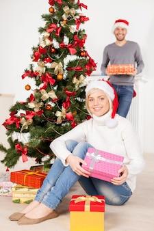 크리스마스 이브에 함께. 크리스마스 모자를 쓴 아름다운 젊은 여성이 나무 근처에 앉아 선물 상자를 들고 남자친구가 배경에 서 있는 동안