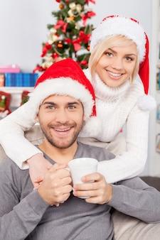 크리스마스 이브에 함께. 크리스마스 모자를 쓴 쾌활한 청년이 컵을 들고 웃고 있는 동안 여자친구가 뒤에 서서 그를 껴안고 있다