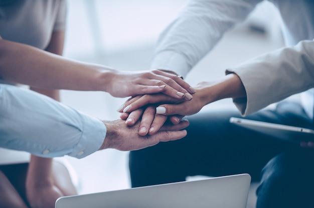 一緒に私たちはすべてを行うことができます!手をつないで、オフィスに座っている間彼らの団結を示す4人の若者のグループの上面図のクローズアップ部分 Premium写真