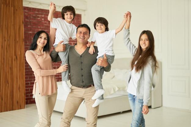 Вместе мы делаем семейный портрет счастливой латинской семьи родителей, девочки-подростка и маленькой девочки.