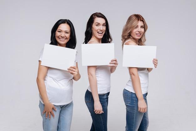 Вместе мы выстоим. изящные, приятные молодые женщины выглядят довольными, позируя вместе в социальной кампании