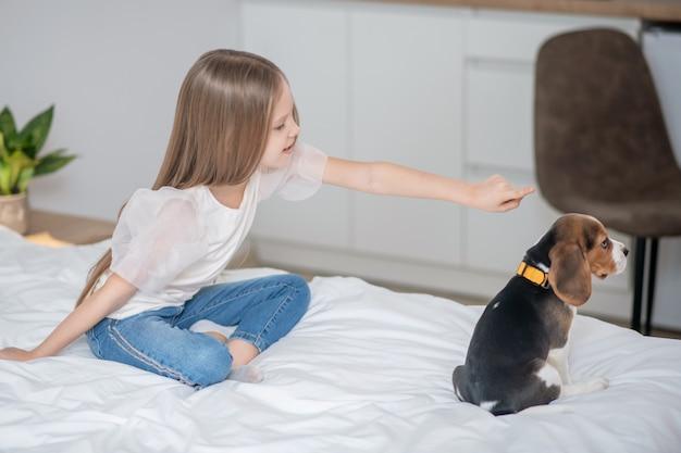 Вместе с питомцем. длинноволосая девочка играет со своим щенком на кровати
