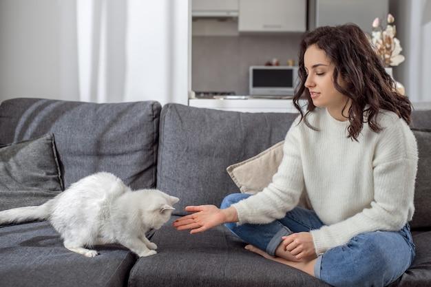 ペットと一緒に。家で週末を過ごし、平和を感じているかわいい若い女性