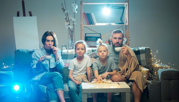Единение счастливая семья смотрит через проектор телевизионные фильмы с попкорном и напитками