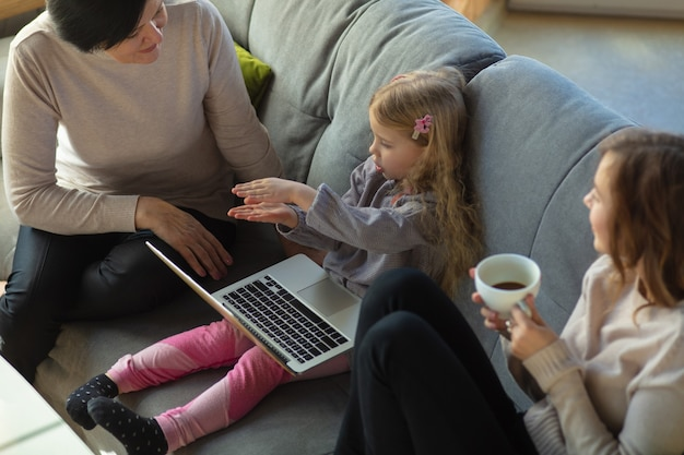 Единение. счастливая любящая семья. бабушка, мать и дочь проводят время вместе. смотрят кино, используют ноутбук, смеются. день матери, праздник, выходные, праздник и концепция детства.