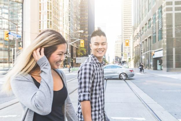 アジアのカップルが街でtogheterを歩く