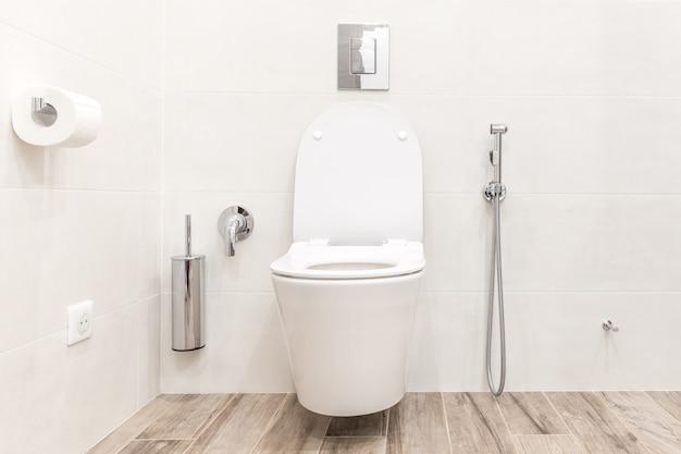 Унитаз в современной белой высокотехнологичной ванной