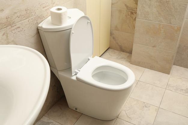 Toilet bowl in modern bathroom in light beige color