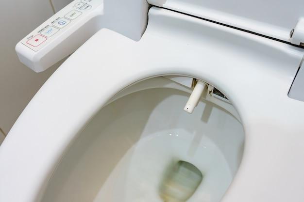 전자 제어 비데가있는 변기. 변기에서 물을 분사합니다.