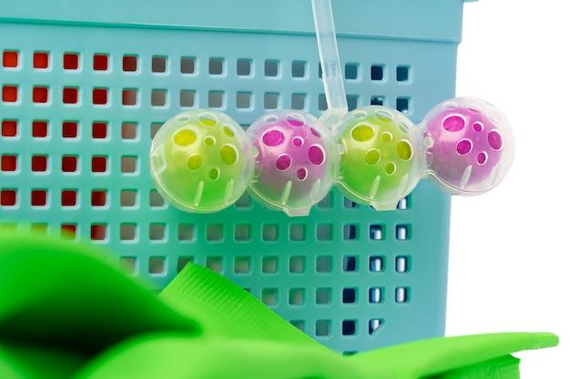 白い背景の上のトイレ掃除洗剤ボールとプラスチックバスケット