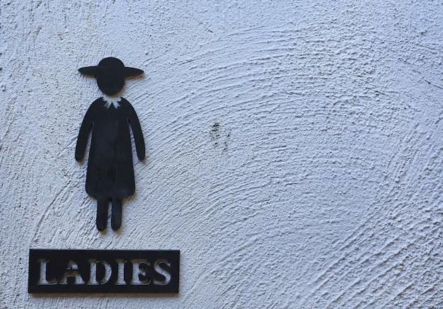 Туалетные знаки женщины на абстрактном фоне белой грубой цементной стены