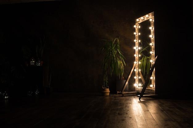 トイレの鏡は木の床に立っており、照明用の電球が付いています。閉じる。