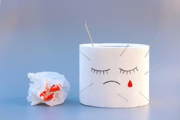 トイレットペーパーと血。痔の治療の概念。
