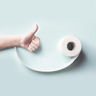 Туалетная бумага и рука поднимая большой палец