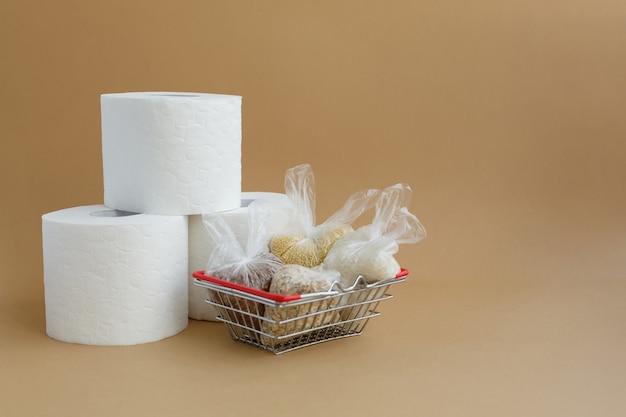 買い物かごに入った小さなビニール袋に入ったトイレットペーパーとさまざまなシリアル 米とオートミール ソバとキビ