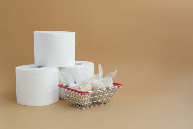 トイレットペーパーと食料品バスケットの小さなビニール袋に入ったさまざまなシリアル米とオートミール