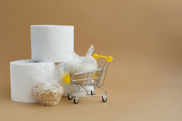 買い物かごに入った小さなビニール袋に入ったトイレットペーパーとさまざまな穀物 米とオートミール