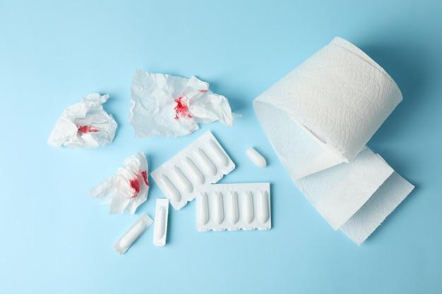 Туалетная бумага, свечи и бумага с кровью на синем, вид сверху