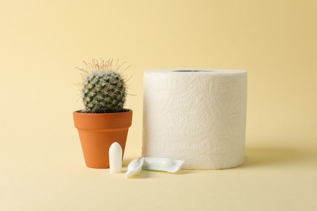 Toilet paper, candles and cactus on beige. hemorrhoids
