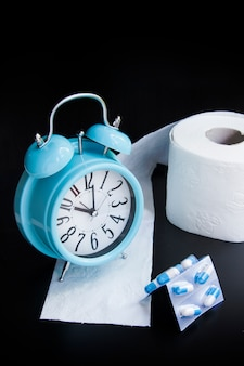 Toilet paper, capsules and alarm clock on black