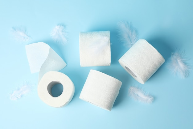 Toilet paper and feathers on blue table, top view