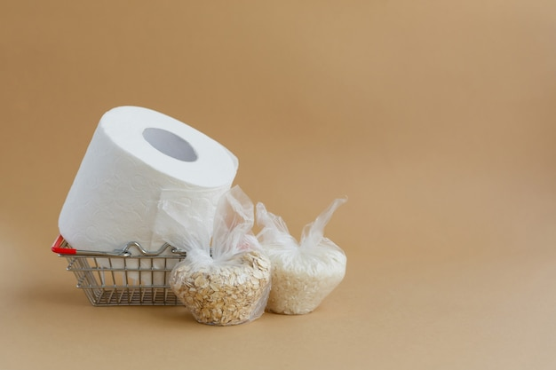 Toilet paper in grocery basket and various cereals in small plastic bags rice and oatmeal