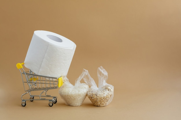 Toilet paper in grocery cart and various cereals in small plastic bags rice and oatmeal