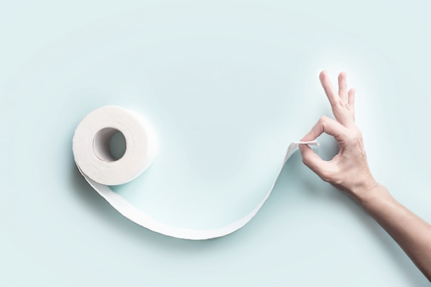 Toilet paper and hand with a gesture ok. form a face with a smile. a concept on the theme of coronavirus