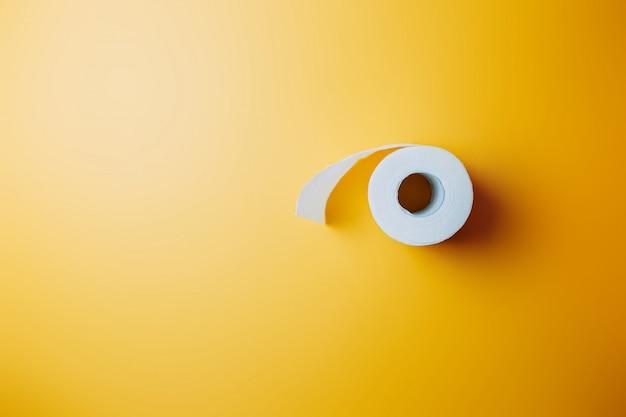 オレンジ色の背景にトイレットペーパー。パンデミック中の白いトイレットペーパーストック。