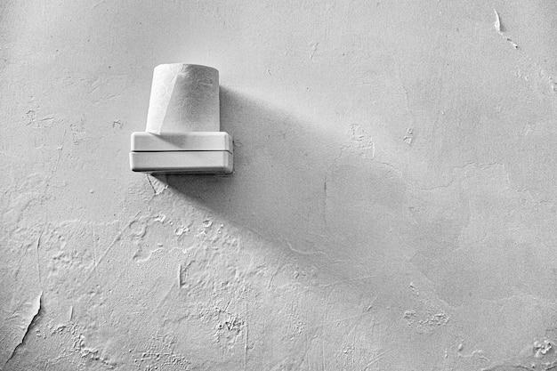 Carta igienica posta sopra una scatola di plastica bianca con un muro bianco sullo sfondo