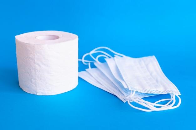 Рулон туалетной бумаги и стерильные защитные маски на синей деревянной стене. туалетная бумага и маска для лица для пандемии covid-19. увеличенный потенциал. высокий спрос