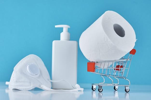 Рулон туалетной бумаги, дезинфицирующее средство антисептический гель и защитная маска на синем фоне. покупательская паника по поводу концепции коронавируса ковид-19.