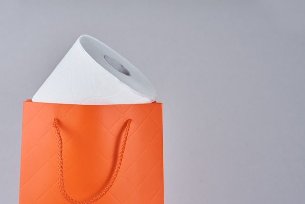 Toilet paper roll in shopping bag as gift on gray background
