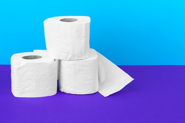 Toilet paper rolls isolated on white table with purple