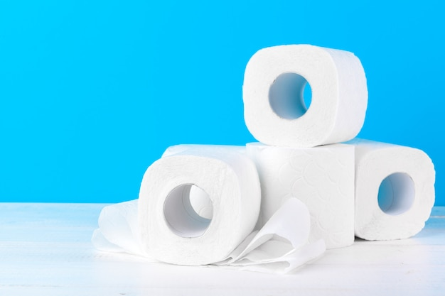 Toilet paper rolls stacked against blue background