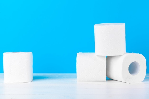 Toilet paper rolls stacked against blue