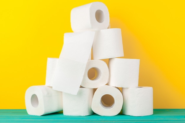 Toilet paper rolls stacked against yellow background