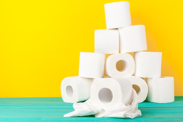Toilet paper rolls stacked against yellow paper