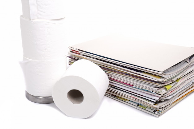 Toilet paper and stack of magazines